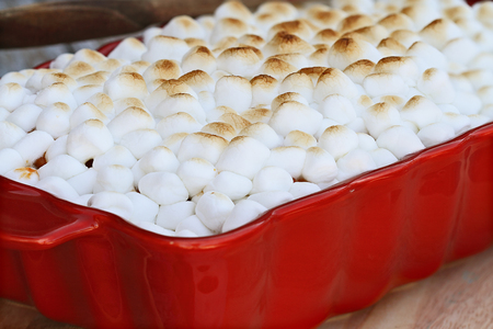 Sweet Potato Casserole baked with mini marshmallows ready for Thanksgiving Day. Extreme shallow depth of field with selective focus. Imagens