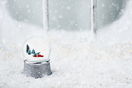Silver snow globe with antique toy truck hauling a Christmas tree. Snowglobe is sitting outdoors on the ledge of an old wooden window in the snow.  Stock Photo