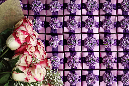 Flat lay of long stem pink and white roses over a background of violet color gift boxes with pretty bows.