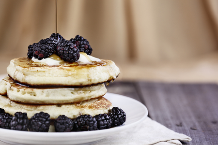 Stack of homemade pancakes with blackberries, melting butter and syrup being poured onto them. Extreme shallow depth of field. Perfect for Shrove Tuesday.