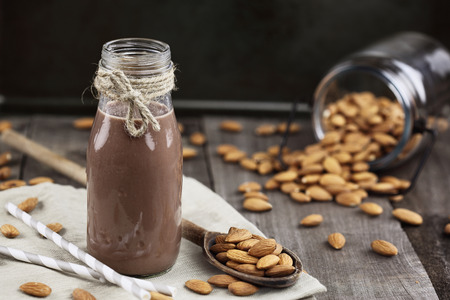 Chocolate almond milk in a glass bottle with whole almonds spilled over a rustic wooden table.