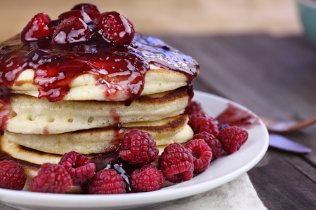 Delicious homemade golden pancakes with fresh raspberries and raspberry syrup. Extreme shallow depth of field.