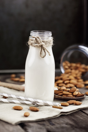 Organic white almond milk in a glass bottle with whole almonds spilled over a rustic wooden table. Stock fotó