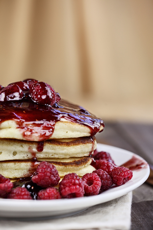 Delicious homemade golden pancakes with fresh raspberries, and raspberry syrup. Extreme shallow depth of field. Stock Photo