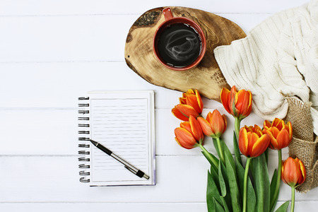 Overhead shot a blank notebook with pen, coffee and a bouquet of orange and yellow tulips over a wood table. Flat lay top view style.