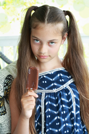 Young girl  child about to eat a chocolate ice cream on a stick.