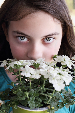 Young teen girl smelling a pot of white Verbena flowers.