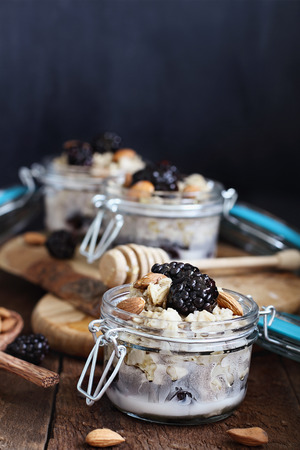 Overnight oatmeal with blackberries, honey and almond milk on a rustic wood background  in a canning glass bail jars with attached lid. Selective focus on oatmeal in front. Banque d'images