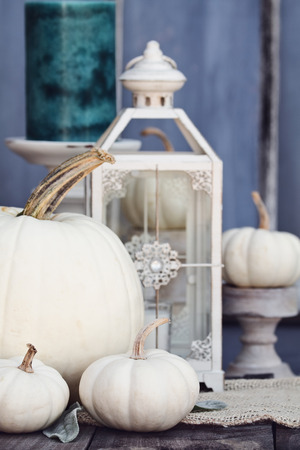 Autumn decorations with heirloom mini and large white pumpkins and candles against a rustic autumn background. Thanksgiving Day or Halloween Decor. Stock Photo - 105601851