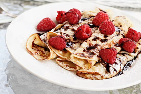 Delicious golden palacinky pancakes or Czech Pancakes with fresh raspberries and sweet chocolate syrup. Extreme shallow depth of field.
