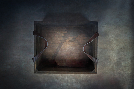 Old rustic wooden box with leather straps over a dark background. Image shot from above. Stock Photo