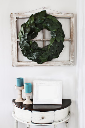 Blank photo frame sitting on a rustic half moon table table below an old farmhouse window decorated with a homemade Magnolia leaf wreath on an interior wall.