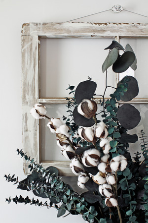Eucalyptus and cotton stem arrangement in front of an old farmhouse window.