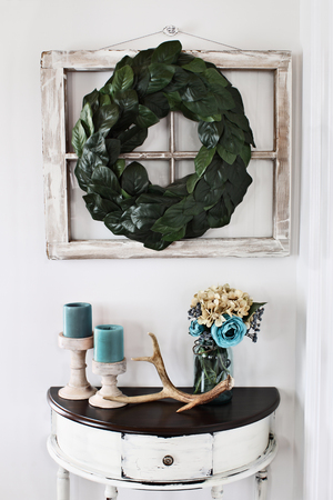 Old farmhouse window decorated with a homemade Magnolia leaf wreath hung on an interior wall over rustic half moon table with candles and flowers decor. Imagens