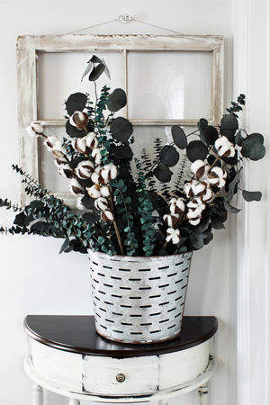 Note to reviewer. Items are all generic. Old olive bucket filled with eucalyptus and cotton stem arrangement on a farmhouse table in front of vintage window.