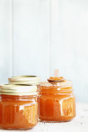 A row of mason jars full of homemade Cantaloupe Jam against a rustic background. Extreme shallow depth of field with selective focus on center jar. Image could also be used for peach jelly or a marmalde.
