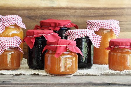 Variety of homemade jams and preserves covered with checkered and red cloth against a rustic background. Extreme shallow depth of field with selective focus on jar in front. Assortment includes peach butter, cantaloupe, blueberry, boysenberry, grape and blackberry.