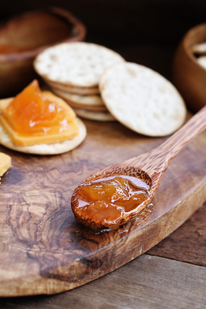 Spoonful of homemade Salted Vanilla Cantaloupe jam with water crackers and cheddar cheese in the background. Stock Photo