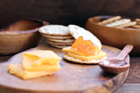 Water cracker, cheddar cheese and homemade Salted Vanilla Cantaloupe jam. Extreme shallow depth of field with selective focus on appetizer in center.