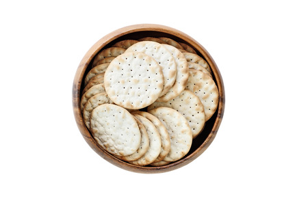Isolated wooden bowl of water crackers over a white background. Clipping path included. Image shot from overhead.