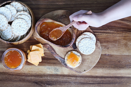 Overhead shot of a womans hand preparing Water cracker, cheddar cheese and homemade savory Salted Vanilla Cantaloupe jam appetizers. Stock Photo