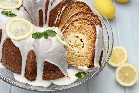 Above shot of lemon cream cheese bundt cake with cream cheese filling in the center cut into slices. Fresh lemons in background. Extreme shallow depth of field.