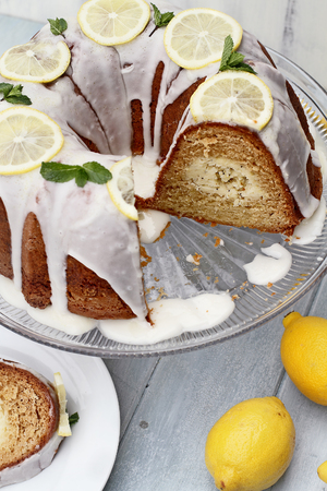Whole lemon cream cheese bundt cake with cream cheese filling in the center and missing slices. Extreme shallow depth of field with selective focus.