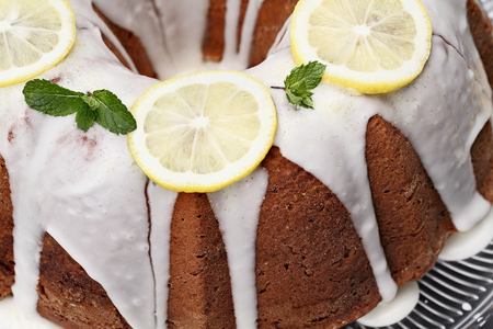 Whole lemon cream cheese bundt cake with slices of fresh lemons and mint on top. Extreme shallow depth of field with selective focus on center of cake.