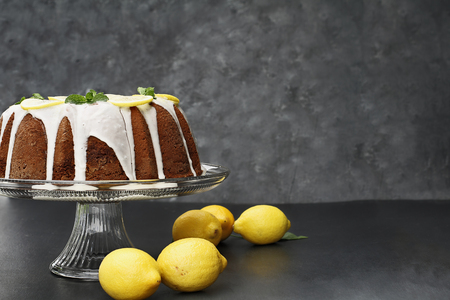 Whole lemon cream cheese bundt cake with slices of fresh lemons and mint on top. Extreme shallow depth of field with selective focus on cake. Free space for text.
