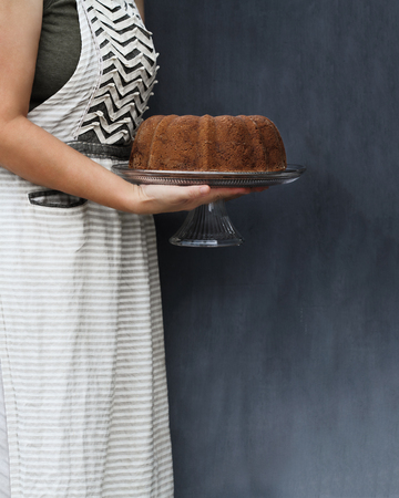 Unrecognizable woman holding a lemon bundt cake and cake stand with hands against rustic background with free space for text. Cake could be used for a number of flavors. Stock Photo