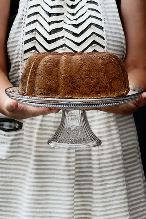 Unrecognizable woman wearing an apron and holding a lemon bundt cake and cake stand in hands. Cake could be used for a number of flavors.