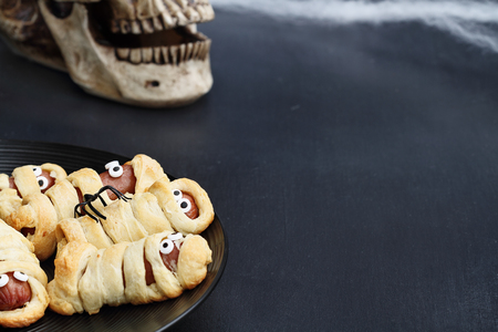Fun food for kids. Halloween mummy hot dogs.  Weiners wrapped in croissant rolls to look like mummies on a plate. Altnerative to candy.