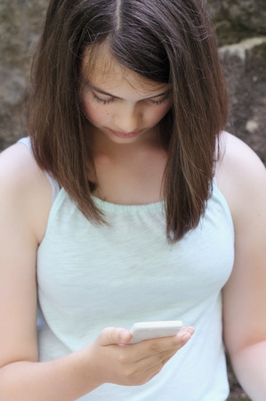 Young teenage girl reading a text message on a smartphone. Selective focus on teens hand holding phone.