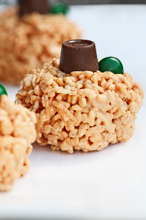 Fun food for kids. Crispy rice and marshmallow treats in the shape of mini pumpkins for Halloween. Stock Photo