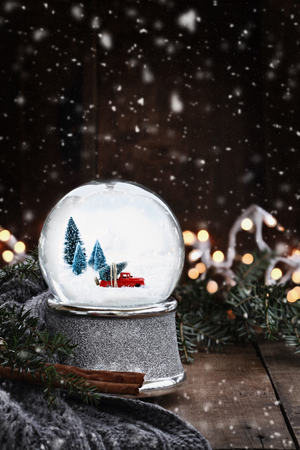 Rustic image of a snow globe with old pick up tuck hauling a Christmas tree surrounded by pine branches, cinnamon sticks and a warm gray scarf with gently falling snow flakes. Stock Photo
