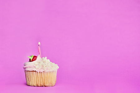 Pretty strawberry or cherry flavored frosted cupcake decorated with white chocolate shavings and one candle burning. Free space for copy text. Stock Photo