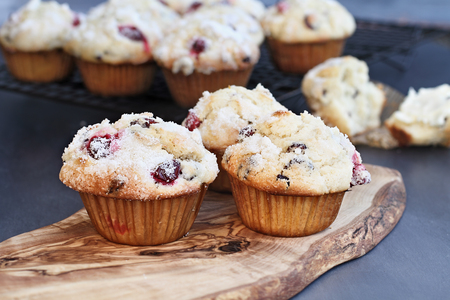 Cranberry Muffins with lemon sugar topping on a rustic cutting board with loose berries. Extreme shallow depth of field with selective focus on muffin in foreground. Stock Photo