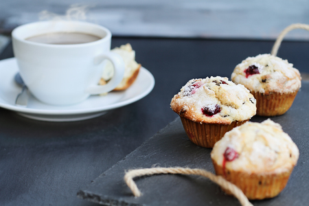 Cranberry Muffins on a slate serving tray with open muffin with butter and a steaming hot cup of coffee in the background. Extreme shallow depth of field with selective focus on center muffin.