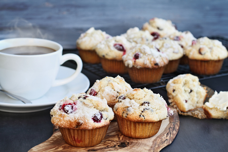 Cranberry Muffins on a wood cutting board with more cooling on a bakers rack. Extreme shallow depth of field with selective focus on center muffin. Steaming hot cup of coffee in the background.