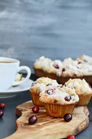 Cranberry Muffins on a wood cutting board with more cooling on a bakers rack. Extreme shallow depth of field with selective focus on muffin in foreground. Steaming hot cup of coffee in the background. Stock Photo