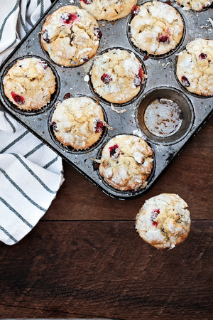 Cranberry Muffins  in a muffin tin with kitchen towel over a rustic wood  background. Free space for text. Stock Photo