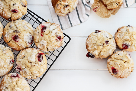 Fresh cranberry muffins cooling on a bakers rack over a rustic white table  background. Image shot from above with free space for text. Stock Photo
