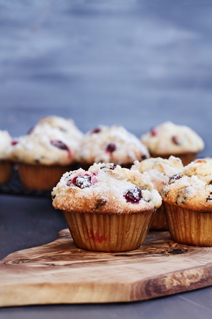 Cranberry Muffins with lemon sugar topping on a rustic cutting board with loose berries. Muffins on cooling rack in background. Extreme shallow depth of field with selective focus on muffin in foreground.