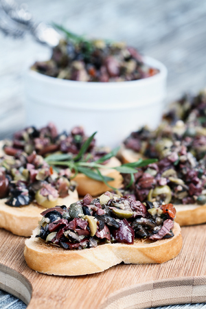 Homemade mixed Olive Tapenade made with garlic, capers, olive oil, Kalamata, black and green olives spread over toasted bread. Shallow depth of field with selective focus on canape. in foreground