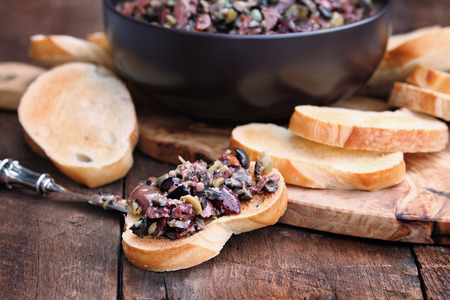 Homemade mixed Olive Tapenade made with garlic, capers, olive oil, Kalamata, black and green olives spread over toasted bread. Extreme shallow depth of field with selective focus on center canape. Stock Photo