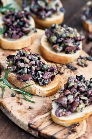 Homemade mixed Olive Tapenade made with garlic, capers, olive oil, Kalamata, black and green olives spread over toasted bread. Extreme shallow depth of field with selective focus on center canape. Archivio Fotografico