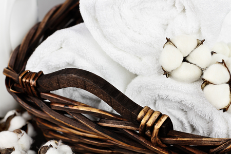 Laundry basket filled white fluffy towels, cotton flowers and a bottle of liquid soap against a blurred grey background. Stock Photo