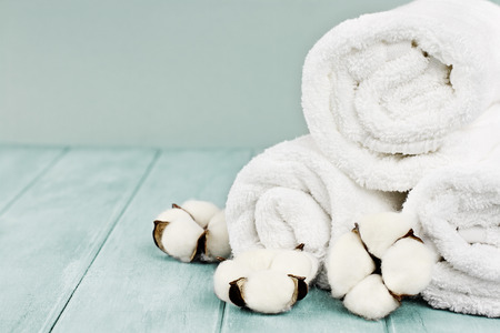 Rolled up white fluffy towels with cotton flowers against a blurred blue background with free space for text. Stock Photo