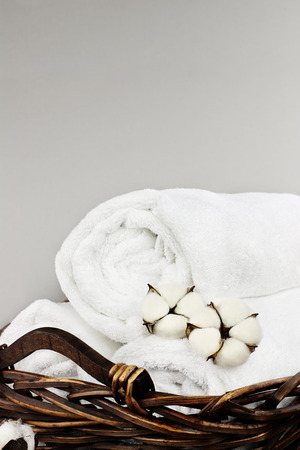 Laundry basket filled white fluffy towels, cotton flowers and a bottle of liquid soap against a grey background with free space for text.