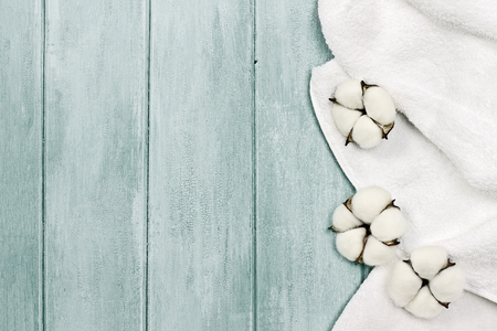 White fluffy towel with cotton boll flowers over a blue green background. Image shot from an overhead top view with free space for text.